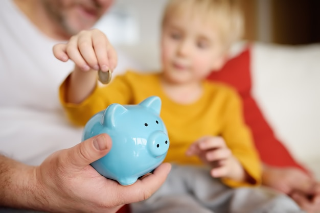 Father and son putting coin into piggy bank