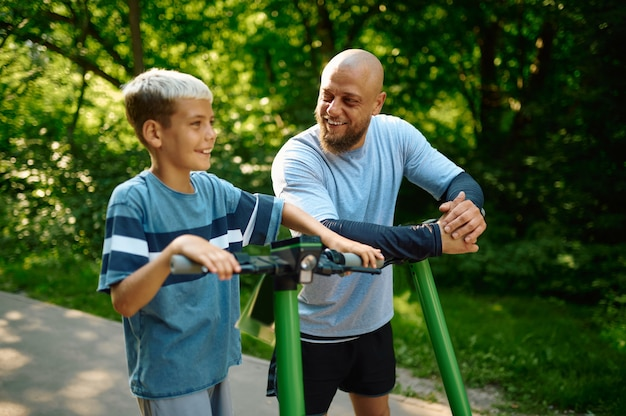 Father and son riding on kick scooters in park