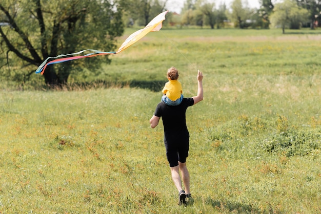 Father and son run in the field with a kite