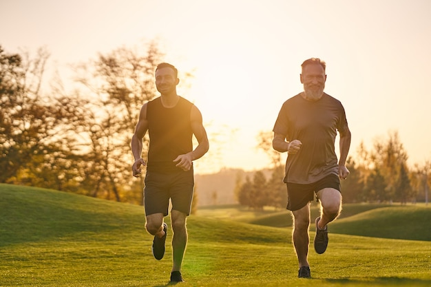 The father and son running in the beautiful park on the sunset background