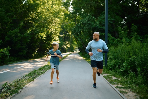 Father and son running on walking path outdoors. the family leads a healthy lifestyle, fitness workout in summer park
