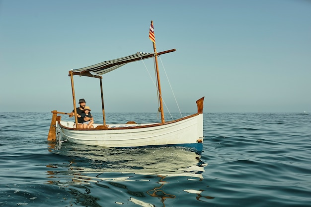 A father and a son sailing in a classic vintage boat