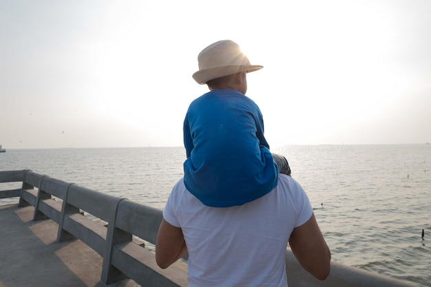 Father and son at sea watching the sunset