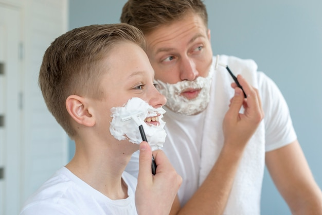Father and son shaving in the mirror