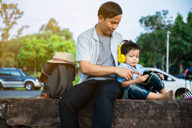 Father and son sit and watch the phone in the park