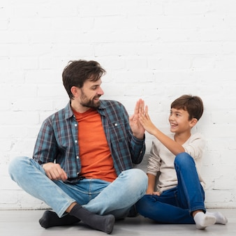 Father and son sitting on floor and high five