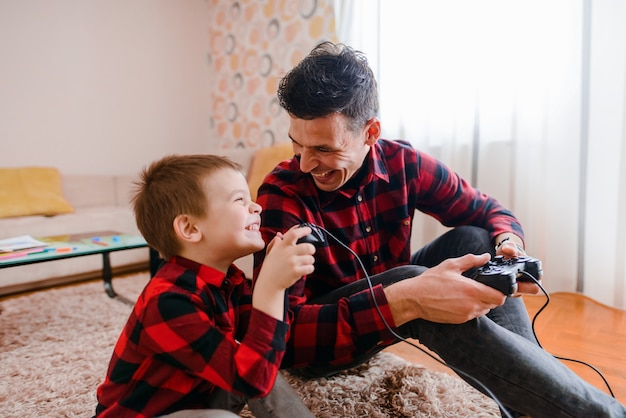 Father and son sitting on floor and playing video games. having fun and smiling.