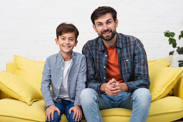 Father and son sitting on sofa and looking at photographer