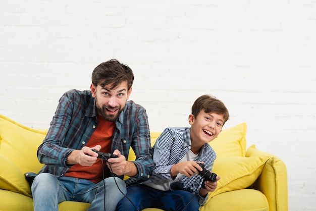 Father and son sitting on sofa and playing on console