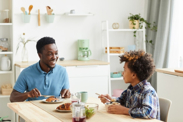 Father and son sitting at the table smiling to each other and having breakfast in the kitchen at home