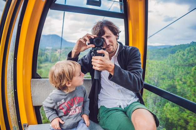 Father and son in ski lift cabin on a cable car