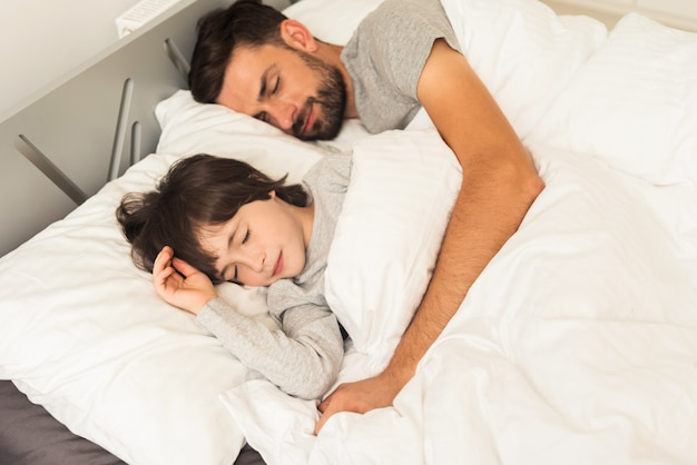 Father and son sleep together on the bed in their house