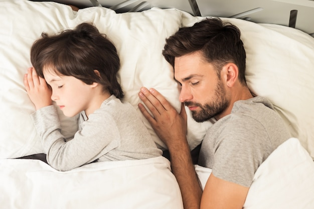 Father and son sleep together on the bed in their house.