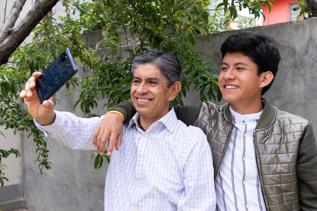 Father and son smile as they take a selfie together