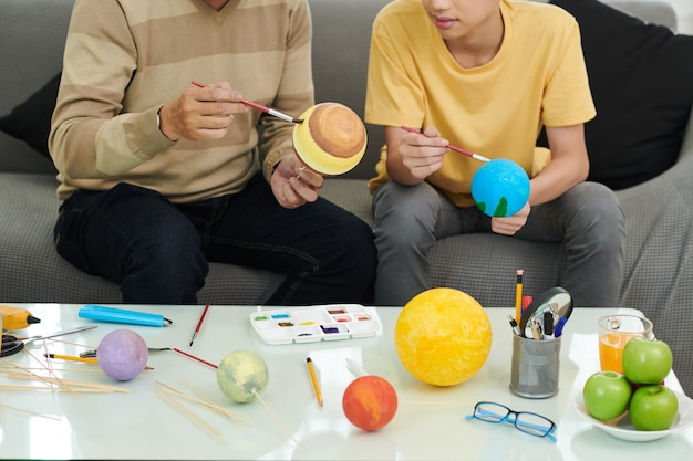 Father and son spending time together, they are paiing balls with various colors to make solar system model for school