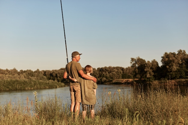 Father and son stand hugging near river wit fishing rods and enjoying beautiful sunset, wearing casual attire, spend time near lake in summer day.