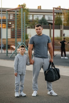 Father and son stand on the sports field after training during sunset