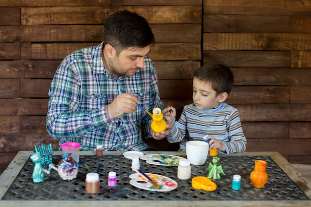 Father and son in the studio of paint a vase.