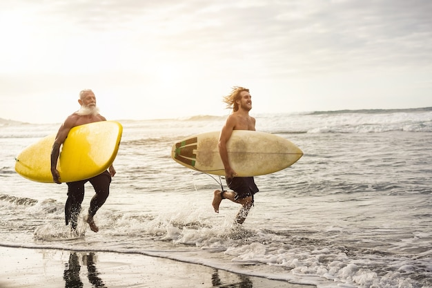 Father and son surfers run along the beach with longboards - focus on senior's board