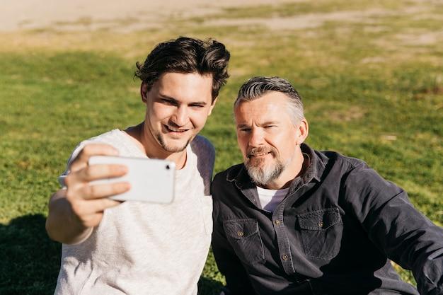 Padre e figlio prendendo selfie in spiaggia