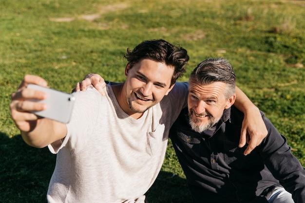 Padre e figlio prendendo selfie sull'erba
