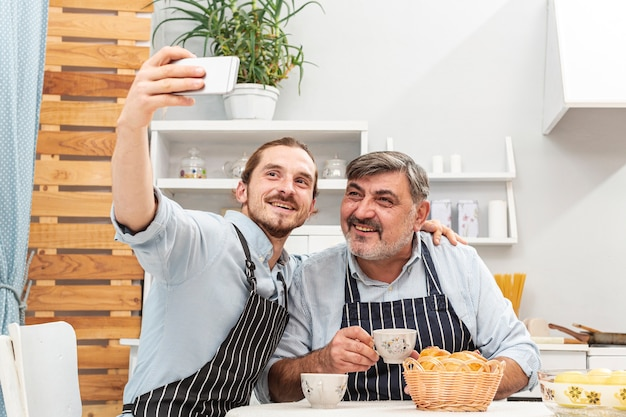 Father and son taking a selfie in kitchen