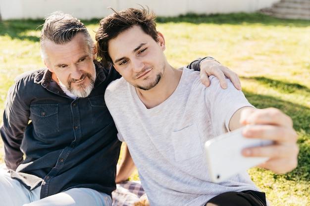 Padre e figlio prendendo selfie in natura