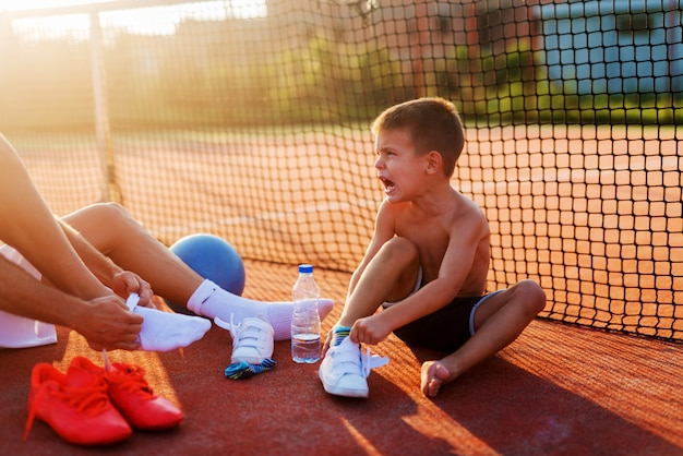 Father and son taking their socks on before tennis training on hot summer day.having fun and smiling.