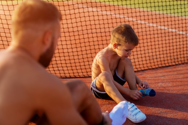 Father and son taking their socks on before tennis training on hot summer day.