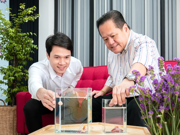 Father and son talking about betta fish in living room.