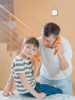 Father and son talking on carrot phones