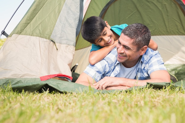 Father and son in their tent in the countryside on a sunny day