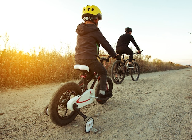 Father and son together are riding bicycles through the pathway in the field