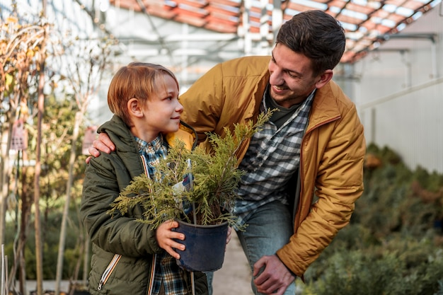 Father and son together buying a small tree
