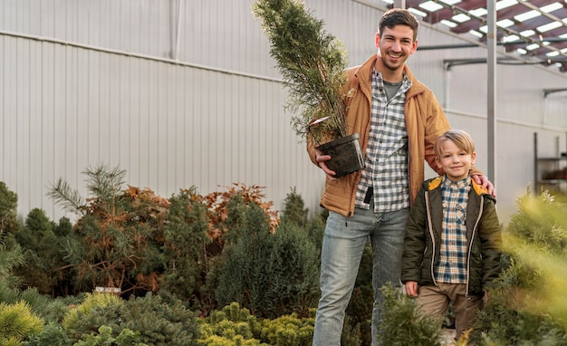 Father and son together at a tree nursery posing with pot