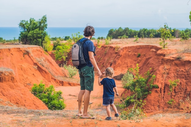 Father and son travelers in red canyon near mui ne, southern vietnam. traveling with children concept.