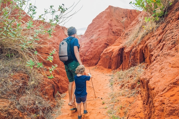 Father and son travelers in red canyon near mui ne, southern vietnam