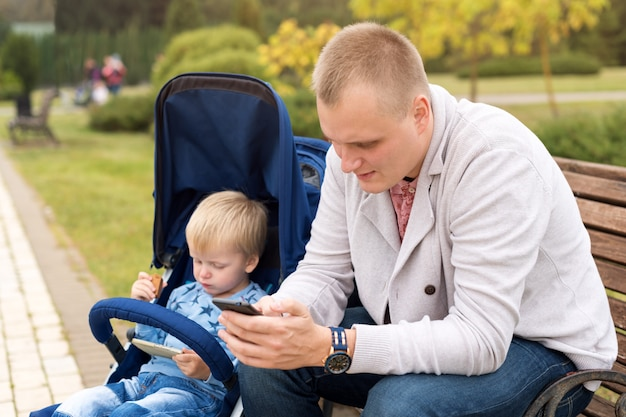 Father and son using smartphones while spending time together in autumn park.