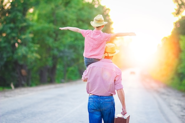 Father and son walk along the road holding hands with suitcase