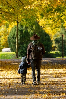 Father and son walk in the park in autumn