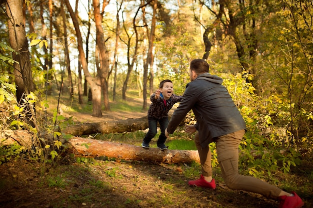 Father and son walking and having fun in autumn forest, look happy and sincere