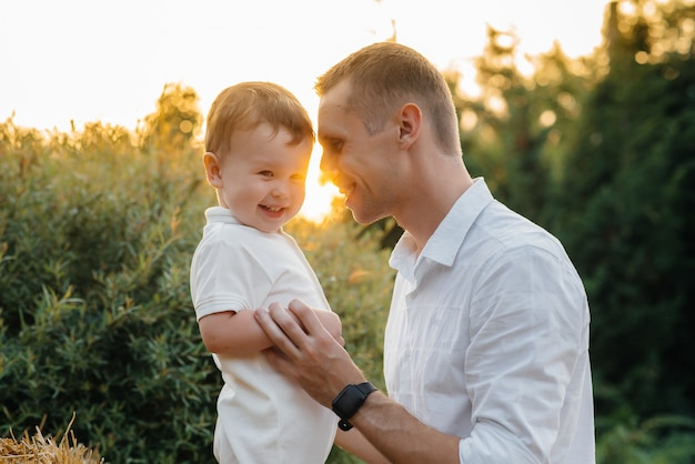 Father and son walking in the park at sunset. happiness. love.