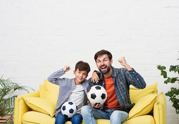 Father and son watching a football match