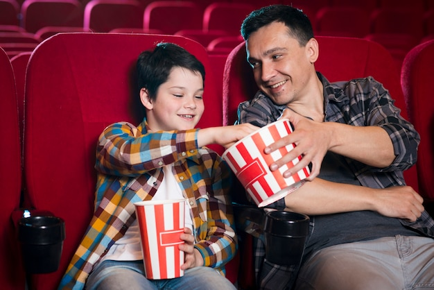 Father and son watching movie in cinema