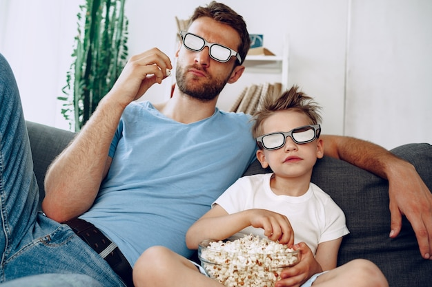 Father and son watching movies at home in 3d glasses and eating popcorn on couch
