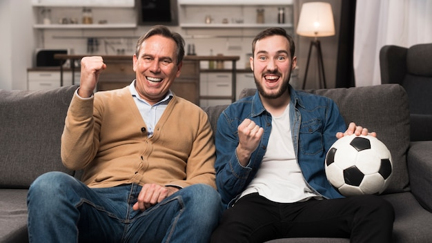 Father and son watching sports in living room