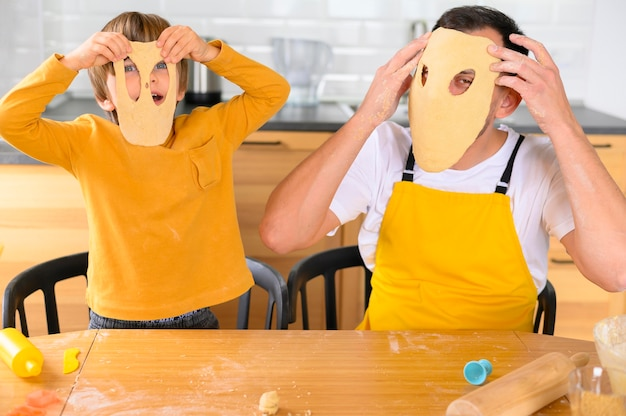 Father and son wearing dough masks