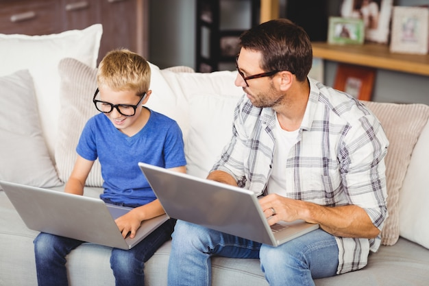 Father and son wearing eyeglasses while working on laptop
