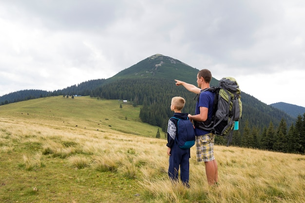 Father and son with backpacks hiking together in summer mountains. back view of dad and child holding hands on landscape mountain view. active lifestyle, family relations, weekend activity concept