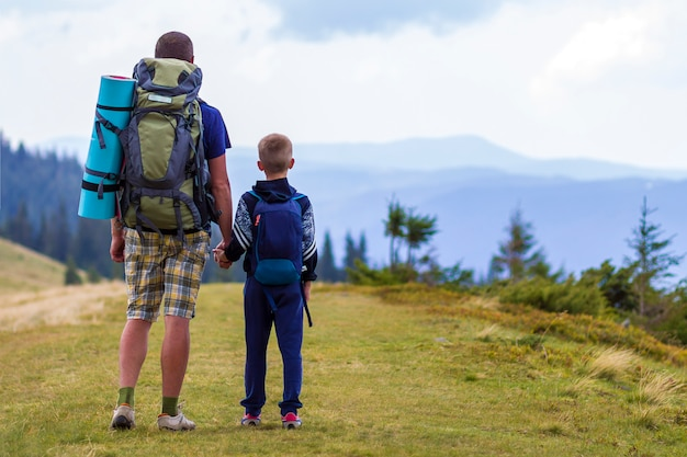 Father and son with backpacks hiking together
